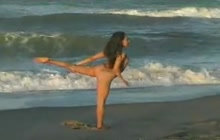 Naked girl doing yoga on the beach